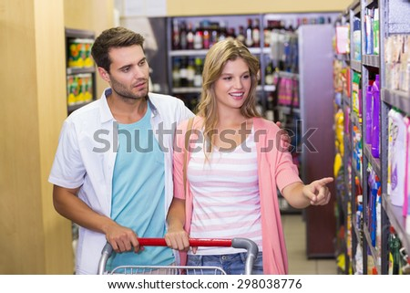 Smiling bright couple showing on shelf at supermaket - stock photo