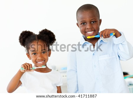 Smiling brother and sister brushing their teeth in the bathroom - stock photo