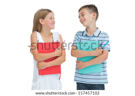 Smiling brother and sister holding their exercise books while posing on white background - stock photo
