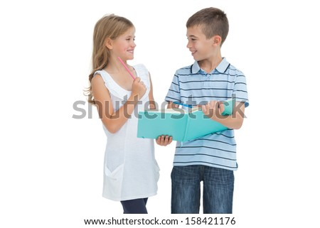 Smiling brother and sister learning their lesson together while posing on white background - stock photo