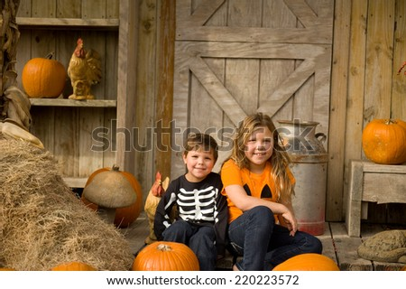 Smiling brother and sister posing in a pumpkin patch for Halloween  - stock photo
