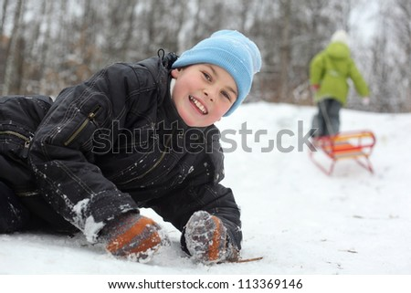 Smiling brother lie on snow, sister pulls sleigh on little hill, focus on brother - stock photo