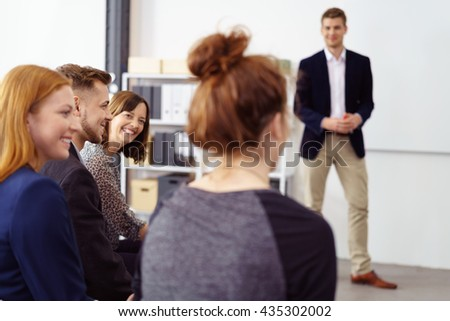 Smiling brown haired woman listening to coworkers during meeting with presenter standing in background with white bulletin board behind him - stock photo