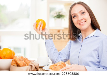 Smiling brunette businesswoman is having healthy breakfast at home - stock photo