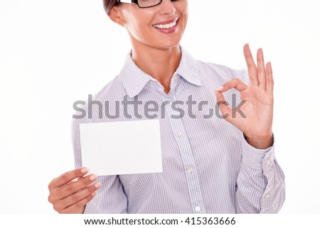 Smiling brunette businesswoman with glasses, wearing her long hair tied back, and a button down shirt, holding a blank copy space in one hand gesturing a perfect sign with the other hand