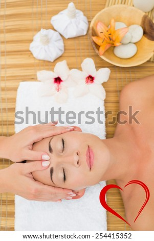 Smiling brunette enjoying a head massage against heart - stock photo