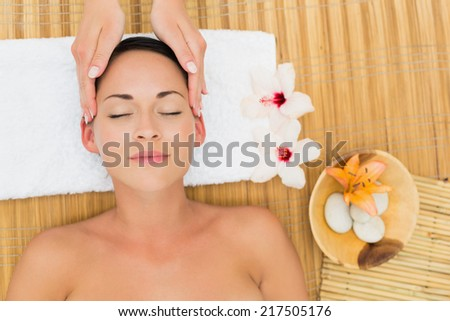Smiling brunette enjoying a head massage in the health spa - stock photo