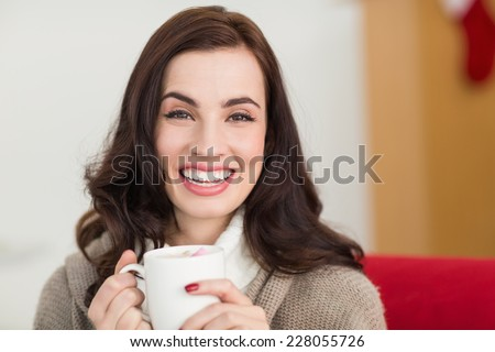 Smiling brunette enjoying a hot chocolate with marshmallow at home in the living room