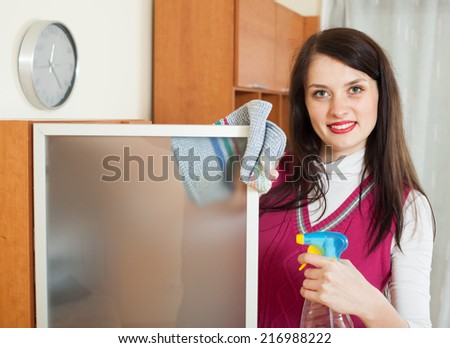 Smiling brunette girl cleaning  glass door of furniture