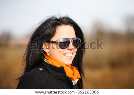 Smiling brunette girl in coat and sunglasses outdoor portrait. - stock photo