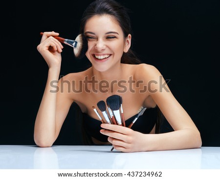 Smiling brunette girl with make up brushes near her face. An attractive girl of European appearance on black background - stock photo