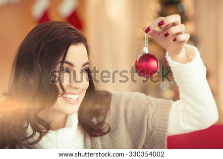 Smiling brunette holding a bauble at christmas at home in the living room - stock photo