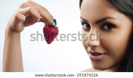 smiling brunette holding a strawberry in hand