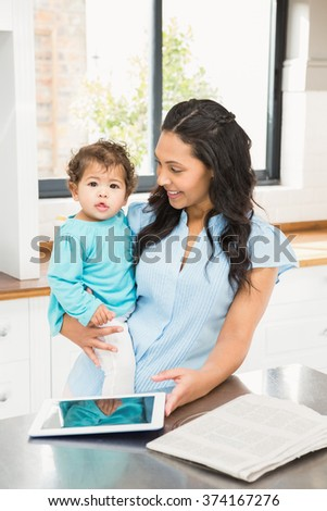 Smiling brunette holding her baby and using tablet in the kitchen - stock photo
