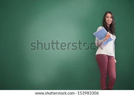 Smiling brunette holding notebook posing green background - stock photo