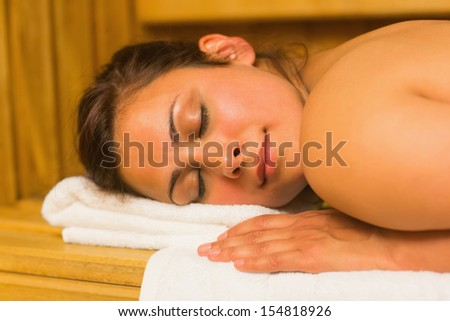 Smiling brunette lying down in a sauna on a white towel - stock photo