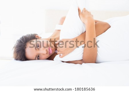 Smiling brunette lying on bed hugging pillow at home in the bedroom