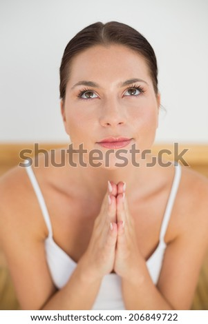 Smiling brunette meditating with hands together in a white room