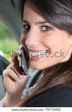 Smiling brunette on a mobile in a car - stock photo