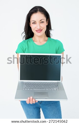 Smiling brunette showing her laptop on white background - stock photo