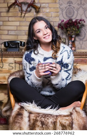 Smiling brunette sitting on the chair with a blue cup - stock photo