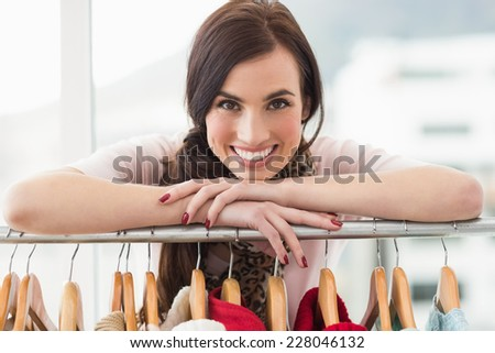 Smiling brunette smiling at camera by clothes rail at clothes store - stock photo