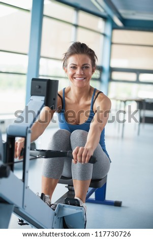 Smiling brunette training on row machine in gym - stock photo