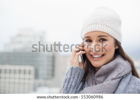 Smiling brunette with winter clothes on having a call outdoors on a cold grey day - stock photo