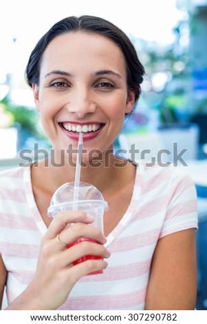 Smiling brunette woman enjoying her milkshake at the coffee - stock photo