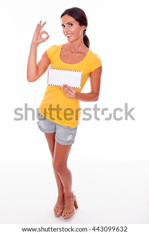 Smiling brunette woman gesturing a perfect sign holding a blank envelope while looking at camera wearing a yellow t-shirt and short jeans isolated