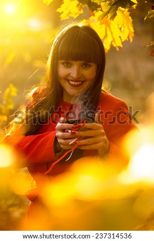 Smiling brunette woman holding evaporating cup of tea at autumn park - stock photo
