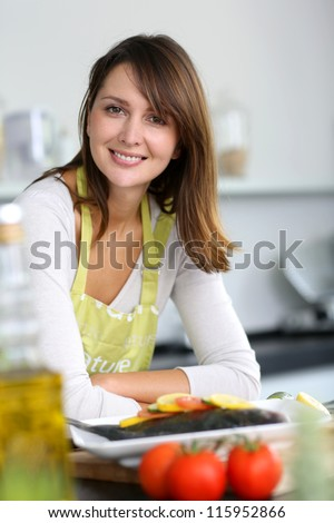 Smiling brunette woman in home kitchen - stock photo