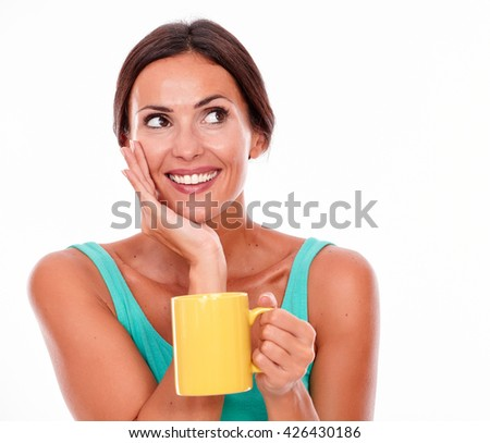 Smiling brunette woman with coffee mug looking away and holding her face wearing a green tank top and her long hair tied back isolated - stock photo