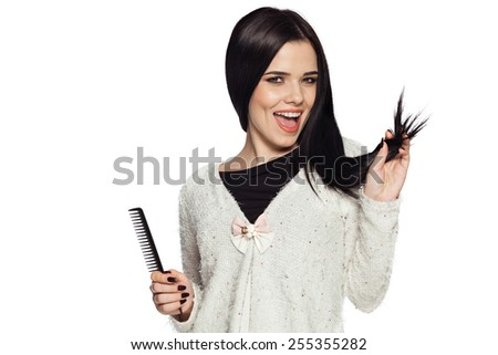 Smiling brunette young woman holding her hair, and a comb.  Gorgeous white caucasian female model feeling happy about her healthy hair. - stock photo