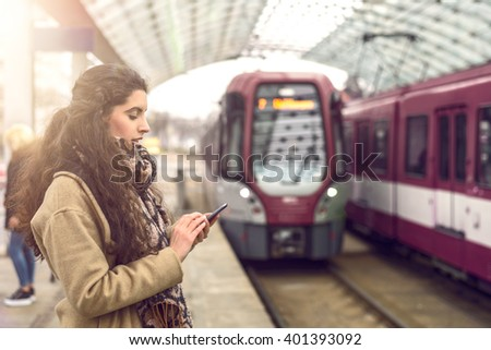 Smiling brunette young woman in coat, standing at station with approaching train while holding her mobile phone - stock photo