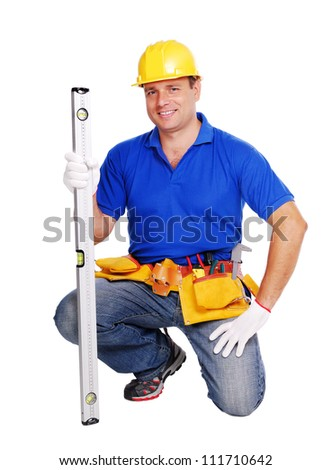 Smiling builder standing on his knee - stock photo