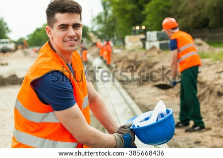 Smiling building worker holding helmet in hand - stock photo