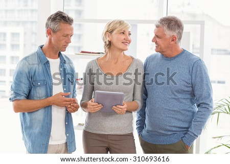 Smiling business colleagues discussing over a tablet at office - stock photo