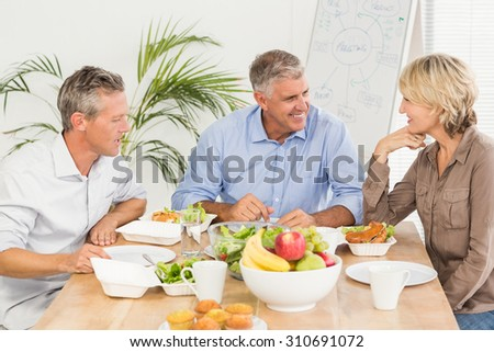 Smiling business colleagues having lunch together at the office - stock photo