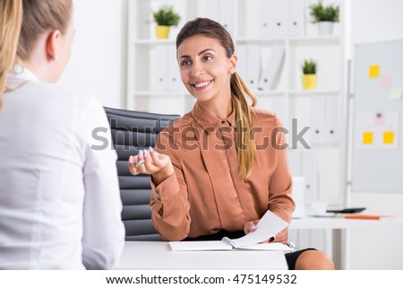Smiling business lady in brown shirt is talking to her blonde colleague. Concept of conversation and business etiquette.