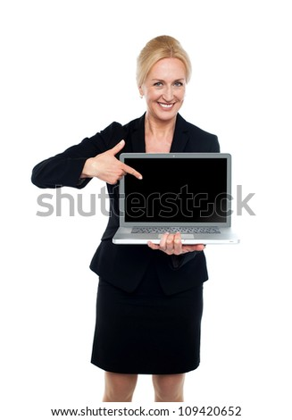 Smiling business lady indicating towards laptop screen isolated over white background - stock photo