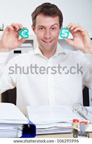 Smiling business man in office holding Dollar and Euro signs - stock photo