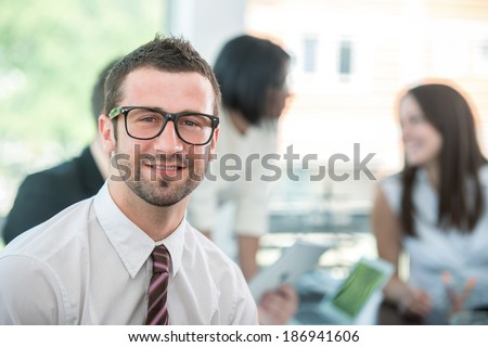 Smiling business man posing in office - stock photo