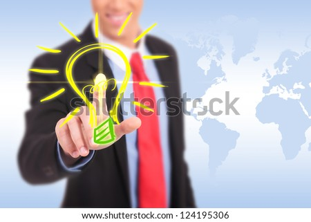 smiling business man pushing a light bulb button having a great idea
