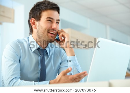 Smiling business man talking on mobile phone in a office - stock photo