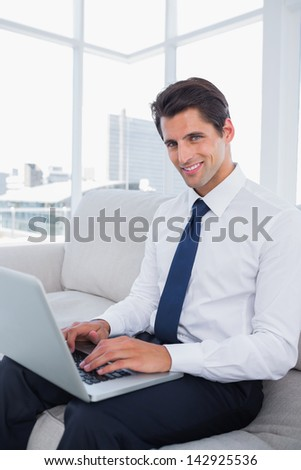 Smiling business man using laptop in a bright office - stock photo