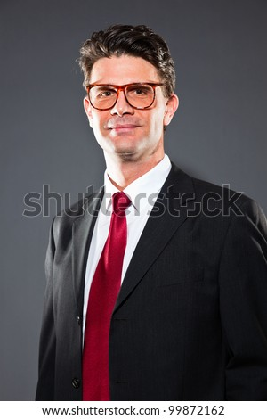 Smiling business man wearing retro glasses with blue suit and red tie isolated on dark background. Studio shot.