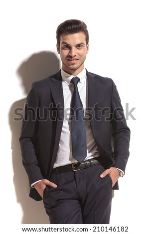 smiling business man with hands in his pockets leaning against white wall