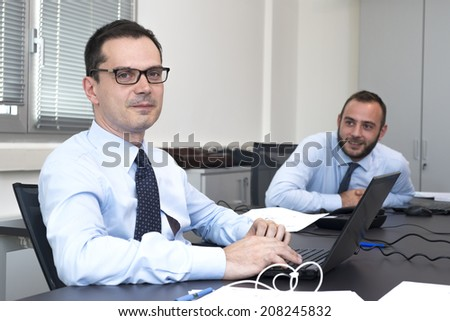 smiling business man working at pc in office - stock photo