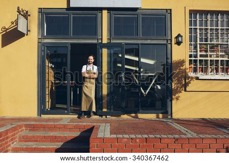 Smiling business owner in front of his shop wearing an apron - stock photo